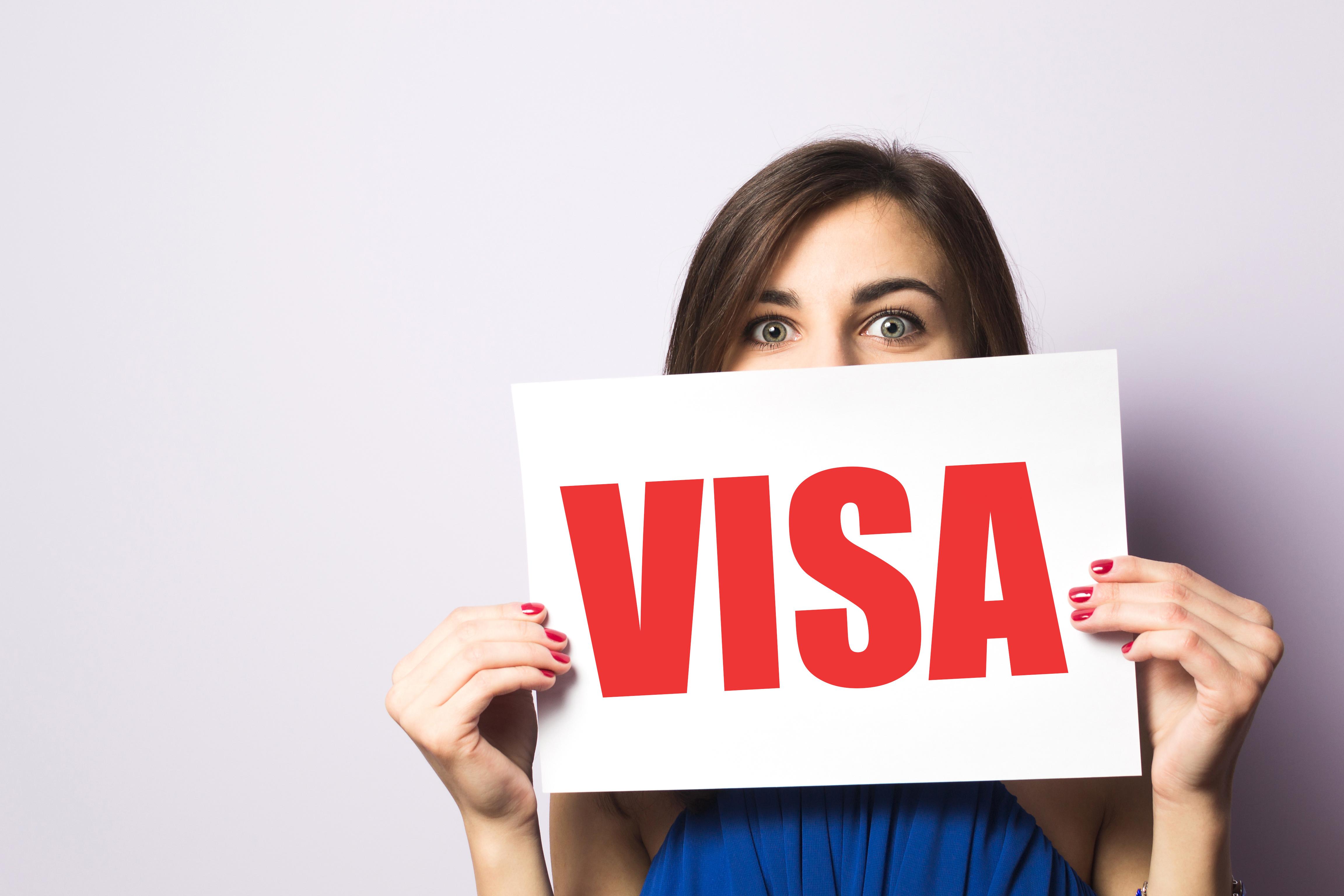 ビザの看板を持つ女性